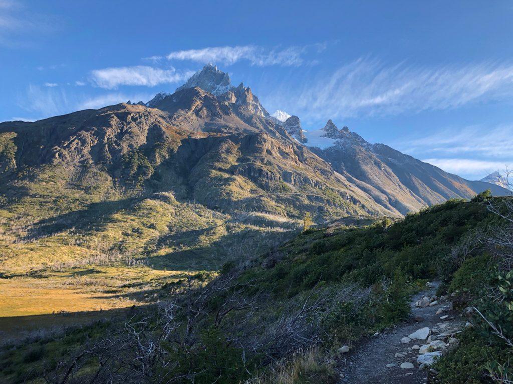 Bild der Landschaft auf dem Weg zum Campamento Italiano mit dem Weg durch Büsche und den Bergen im Hintergrund.